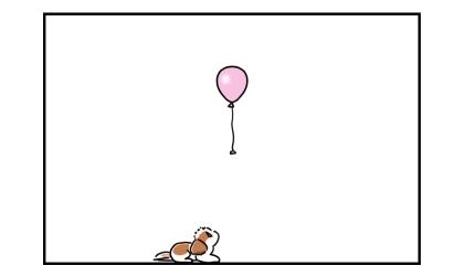 だいぶ降りてきた風船を伏せして見つめる犬